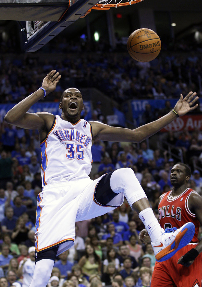 Photo -   Oklahoma City Thunder forward Kevin Durant (35) reacts after a dunk in front of Chicago Bulls forward Luol Deng, right, in the third quarter of an NBA basketball game in Oklahoma City, Sunday, April 1, 2012. (AP Photo/Sue Ogrocki)