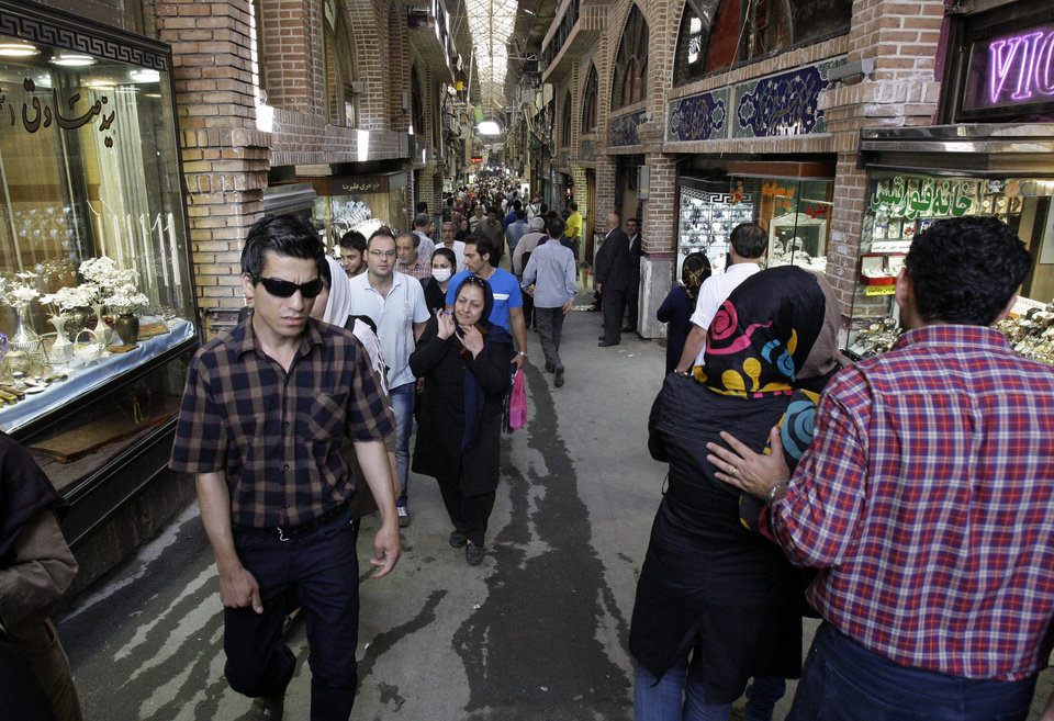 Photo -   In this picture taken on Saturday, July 14, 2012, Iranians make their way in the main bazaar in Tehran, Iran. Police threatened merchants who closed their shops in Tehran's main bazaar and launched crackdowns on sidewalk money changers on Wednesday, Oct. 3, 2012 as part of a push to halt the plunge of Iran's currency, which has shed more than a third its value in less than a week. (AP Photo/Vahid Salemi)