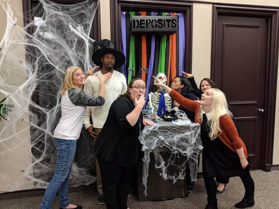 Photo -  The First State Bank employees celebrate winning the best door decoration on Halloween. [Photo provided]