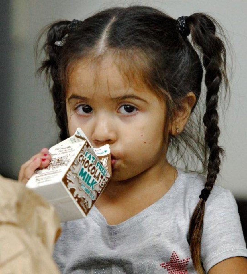 Photo - Jaqueline (cq) Munoz, 4, drinks chocolate milk with other children during an afternoon meal.   JIM BECKEL - THE OKLAHOMAN