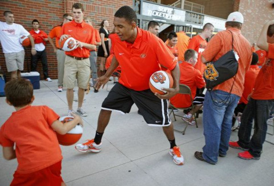 Photo - OSU freshman Le'Bryan Nash plays basketball with fans before a college football game between the Oklahoma State University Cowboys (OSU) and the University of Arizona Wildcats at Boone Pickens Stadium in Stillwater, Okla., Thursday, Sept. 8, 2011. Photo by Bryan Terry, The Oklahoman  BRYAN TERRY