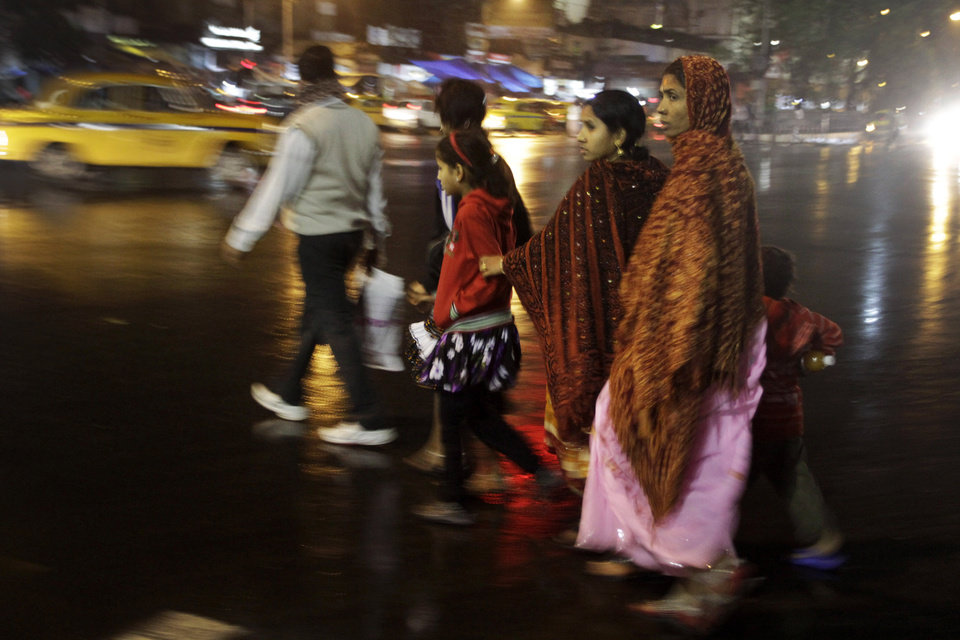 An Indian family crosses a busy road after a rain shower in Kolkata, India, Sunday, Feb. 17, 2013. Rains lashed most parts of north India bringing down the temperatures. (AP Photo/Bikas Das)