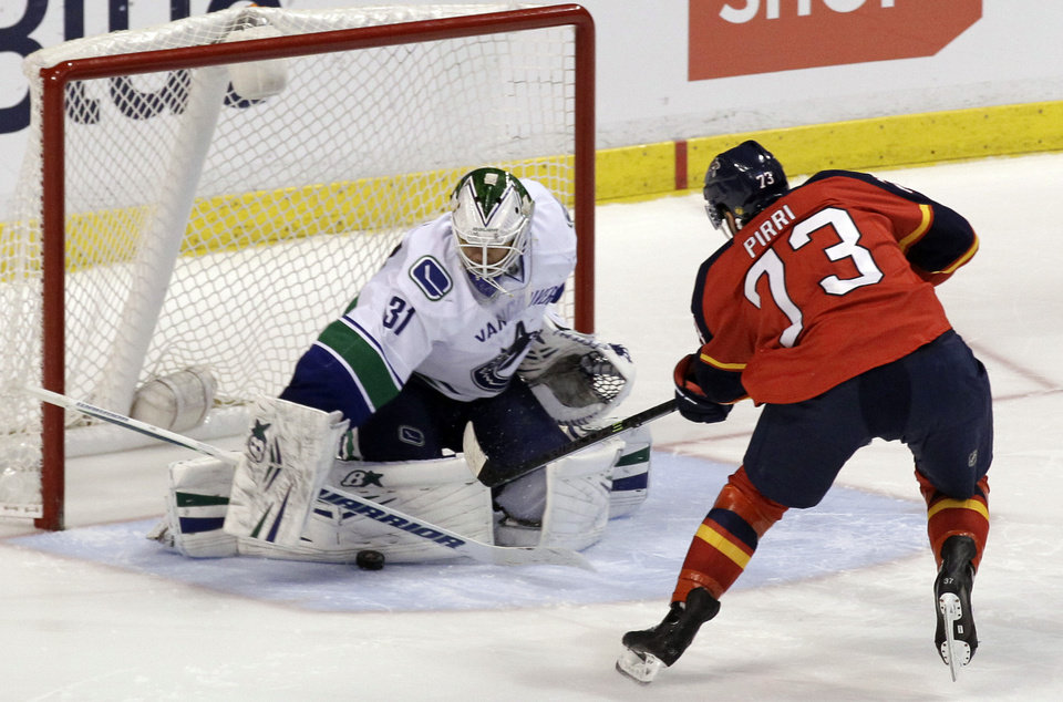 Photo - Vancouver Canucks goalie Eddie Lack (31), of Sweden, blocks a shot by Florida Panthers' Brandon Pirri (73) during a shootout of an NHL hockey game on Sunday, March 16, 2014, in Sunrise, Fla. The Canucks won 4-3. (AP Photo/Luis M. Alvarez)