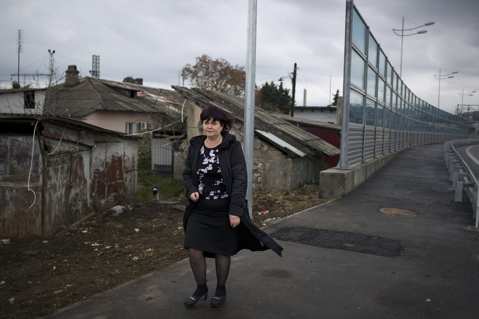 Photo - In this photo taken on Wednesday, Nov. 27, 2013, Irina Kharchenko walks away from her house beside the screen separating the yard of her house and a federal highway in the village Vesyoloye outside Sochi, Russia. As the Winter Games are getting closer, many Sochi residents are complaining that their living conditions only got worse and that authorities are deaf to their grievances. (AP Photo/Alexander Zemlianichenko)