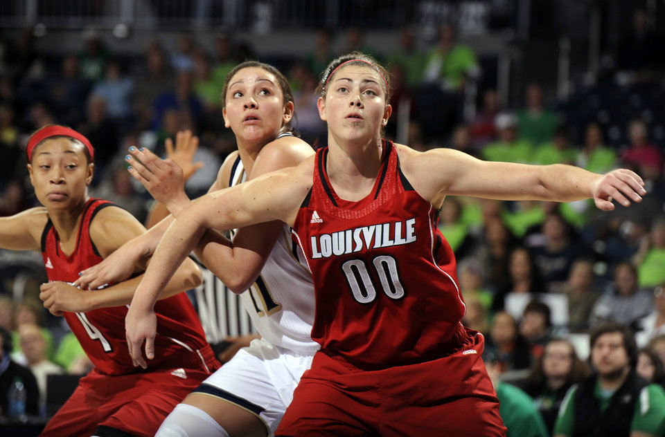 Photo - Louisville forward Sara Hammond, right, battles for a rebound with Notre Dame forward Natalie Achonwa, center, and Louisville guard Antonita Slaughter in the first half of an NCAA college basketball game, Monday, Feb. 11, 2013, in South Bend, Ind. (AP Photo/Joe Raymond)