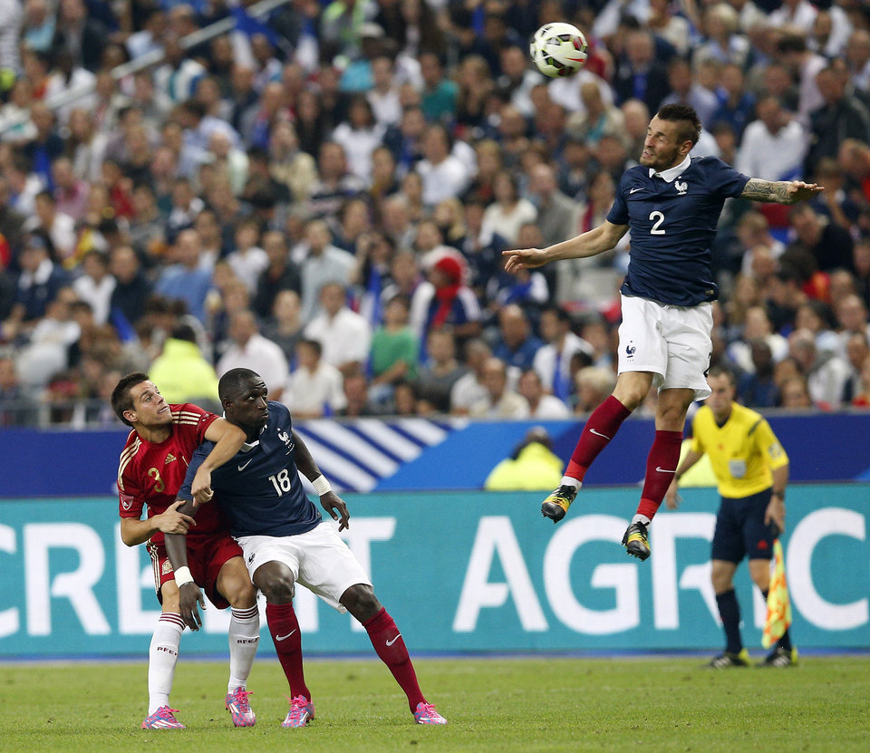 Photo - France's Mathieu Debuchy, right, jumps for the ball, as France's Moussa Sissoko, center, and Spain's David Azpilicueta look on during their international friendly soccer match at the Stade de France in Saint Denis, outside Paris, Thursday, Sept. 4, 2014. (AP Photo/Christophe Ena)