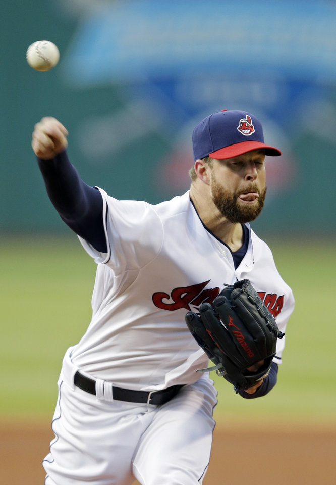 Photo - Cleveland Indians starting pitcher Corey Kluber delivers against the Cincinnati Reds in the first inning of a baseball game Monday, Aug. 4, 2014, in Cleveland. (AP Photo/Mark Duncan)