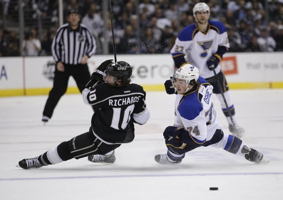 Photo - Los Angeles Kings' Mike Richards, left, and St. Louis Blues' T.J. Oshie fall to the ice during the third period in Game 6 of a first-round NHL hockey Stanley Cup playoff series in Los Angeles, Friday, May 10, 2013. The Kings won 2-1. (AP Photo/Jae C. Hong)