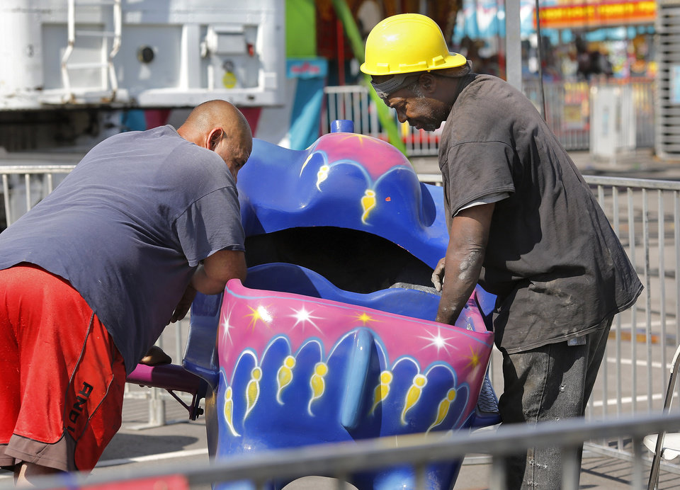 Photo - Workers prepare the surface of the seats on a children's ride before applying touch-up paint. Crews spent most of Wednesday, Sep 13, 2017, putting finishing touches on rides and exhibits in advance of the opening of the 2017 Oklahoma State Fair on Thursday.  Photo by Jim Beckel, The Oklahoman
