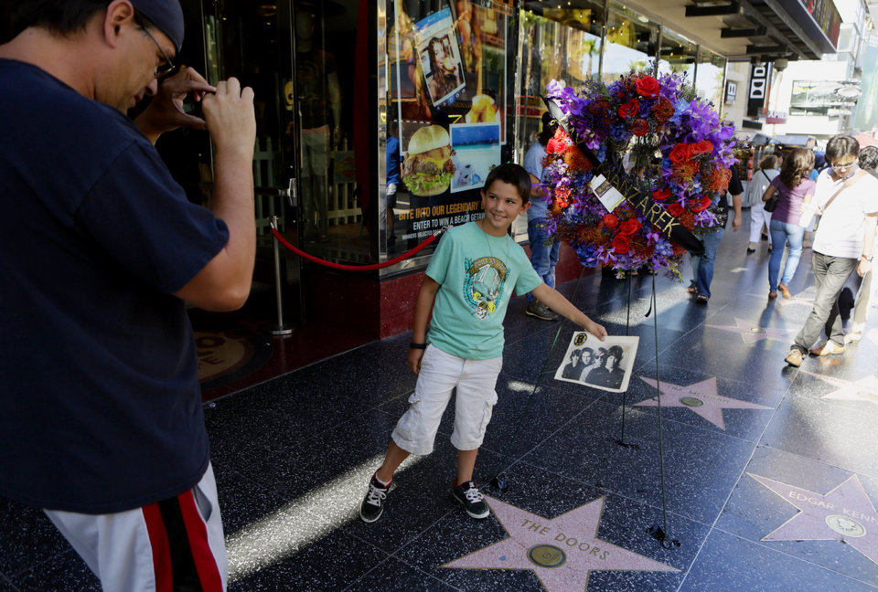 Photo - Darron Quigley,left, takes a photo of his son Jack Quigley, 8, from Simi Valley, Calif., in front of flowers placed on the Hollywood Walk of Fame star of Ray Manzarek of The Doors today, Monday, May 20, 2013, in Los Angeles Monday, May 20, 2013. Ray Manzarek, the keyboardist and founding member of The Doors who had a dramatic impact on rock 'n' roll, has died. He was 74. (AP Photo/Damian Dovarganes)