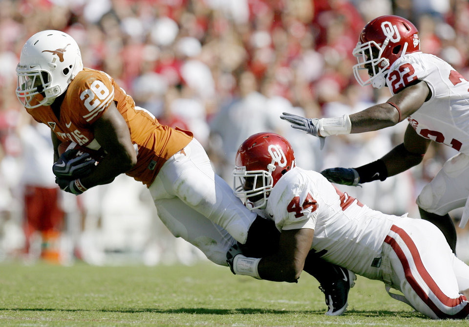 Photo - Fozzy Whittaker of Texas is brought down by OU's Jeremy Beal, center, as Keenan Clayton chases during the Red River Rivalry college football game between the University of Oklahoma Sooners (OU) and the University of Texas Longhorns (UT) at the Cotton Bowl in Dallas, Texas, Saturday, Oct. 17, 2009. Photo by Bryan Terry, The Oklahoman