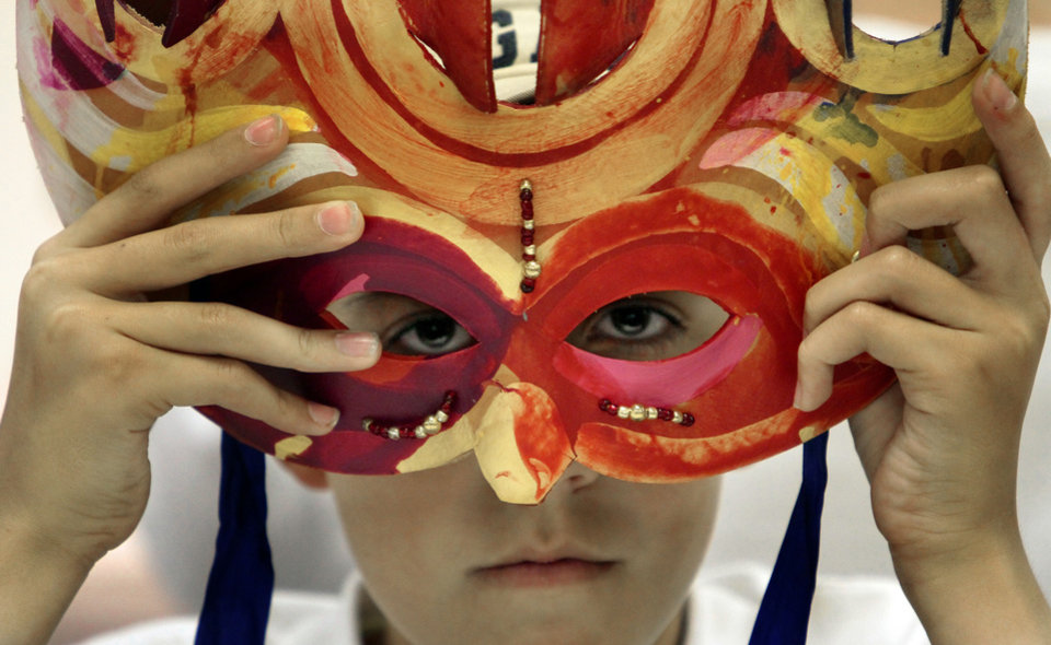 Photo - Nicholas Almond, 12, looks through a mask created by Patrick Riley at a mask-making workshop Tuesday at Norman Public Library. PHOTOS BY STEVE SISNEY, THE OKLAHOMAN
