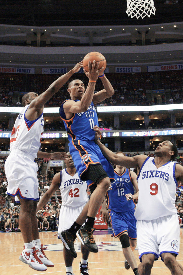 Photo - Oklahoma City's Russell Westbrook, center, goes up for a shot against Philadelphia's Jodie Meeks, left, and Andre Iguodala. AP photo