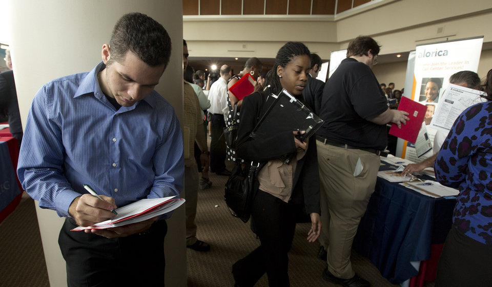 Photo - In this Tuesday, Jan. 22, 2013 photo, Fernando Rames answers questions on a job application at the job fair in Sunrise, Fla. U.S. employers added 157,000 jobs in January, and hiring was much stronger at the end of 2012 than previously thought, providing reassurance that the job market held steady even as economic growth stalled, according to Labor Department reports, Friday, Feb. 1, 2013. (AP Photo/J Pat Carter)