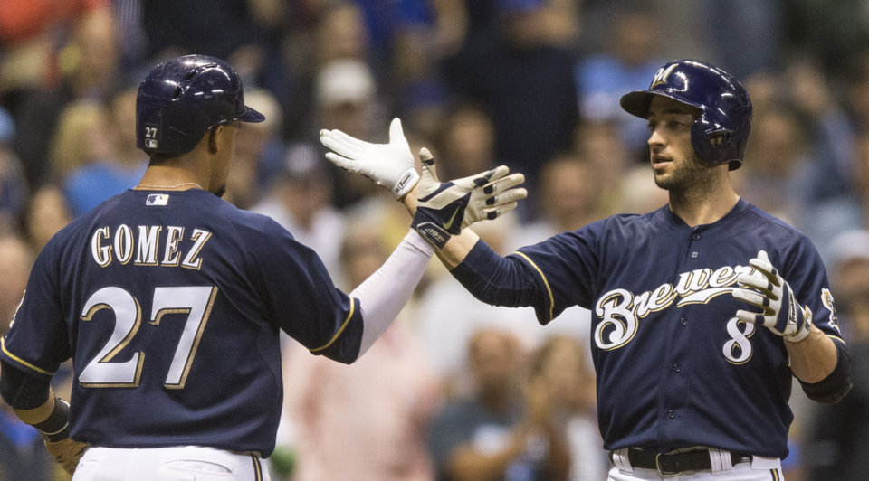 Photo - Milwaukee Brewers' Carlos Gomez (27) greets teammate Ryan Braun after Braun hit a two-run home run off New York Mets' Daisuke Matsuzaka during the seventh inning of a baseball game on Thursday, July 24, 2014, in Milwaukee. (AP Photo/Tom Lynn)