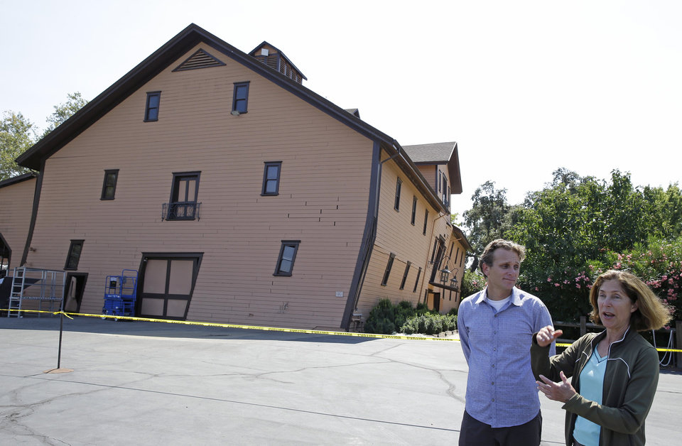 Photo - Owner Janet Trefethen, right, and president Jon Ruel, left, talk about the earthquake damage to the historic winery building, seen in the background, dating from 1886 at Trefethen Family Vineyards Monday, Aug. 25, 2014, in Napa, Calif. The winery is hopeful they can save the building after San Francisco Bay Area's strongest earthquake in 25 years struck the heart of California's wine country early Sunday. (AP Photo/Eric Risberg)