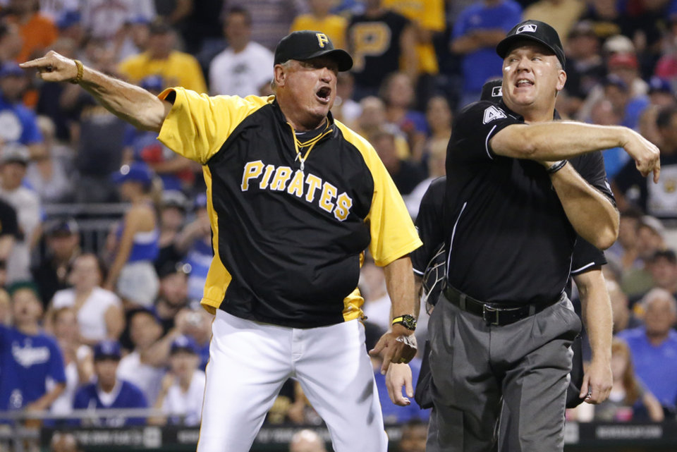 Photo - Umpire Jeff Nelson, right, ejects Pittsburgh Pirates manager Clint Hurdle during the seventh inning of a baseball game against the Los Angeles Dodgers in Pittsburgh Tuesday, July 22, 2014. Hurdle objected to Pirates relief pitcher Justin Wilson being ejected for hitting Los Angeles Dodgers' Justin Turner. (AP Photo)