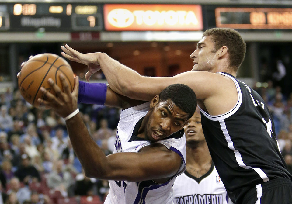Photo - Sacramento Kings forward Jason Thompson, left, pulls a rebound away from Brooklyn Nets center Brook Lopez during the first quarter of an NBA basketball game in Sacramento, Calif., Wednesday, Nov. 13, 2013. (AP Photo/Rich Pedroncelli)