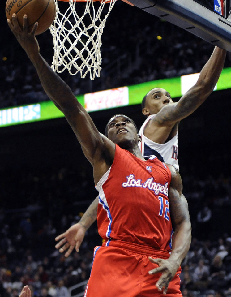 Los Angeles Clippers' Eric Bledsoe (12) scores over Atlanta Hawks' Jeff Teague (0) in the second half of an NBA basketball game at Philips Arena in Atlanta, Saturday, Nov. 24, 2012. Atlanta won 104-93. (AP Photo/David Tulis)