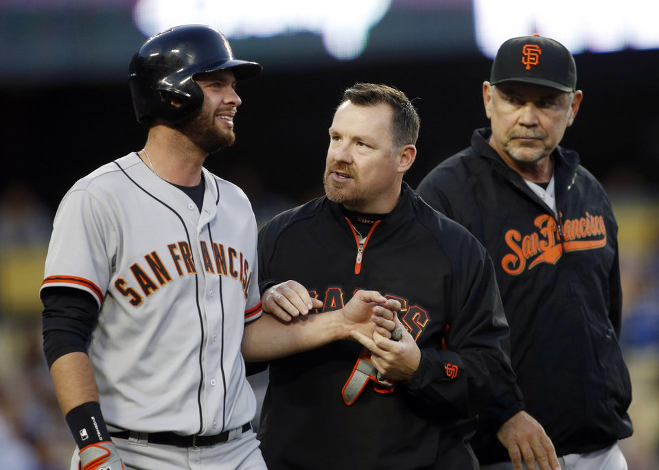 Photo - San Francisco Giants' Brandon Belt, left, reacts after being hit by a pitch on his left hand as a trainer and manager Bruce Bochy, right, attend to him against the Los Angeles Dodgers during the second  inning of a baseball game, Friday, May 9, 2014, in Los Angeles. (AP Photo/Danny Moloshok)