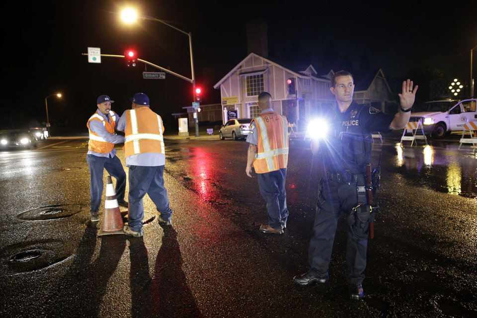 Photo - A police officer controls the traffic as workers shut off the water valve on Friday, March 28, 2014, in Fullerton, Calif. A magnitude-5.1 earthquake was widely felt in the Los Angeles area and surrounding counties Friday evening, but authorities said there were no immediate reports of significant damages or injuries. (AP Photo/Jae C. Hong)