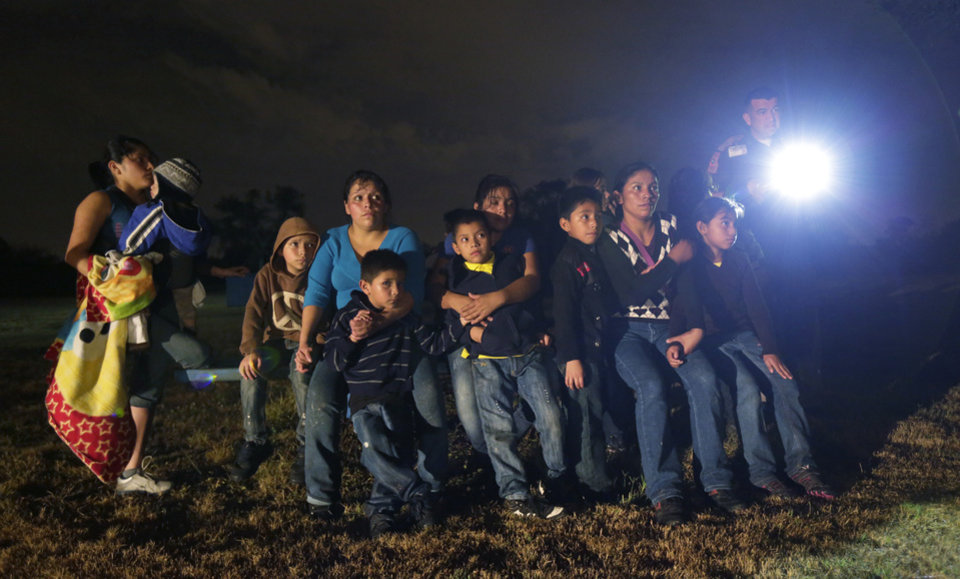Photo - FILE - In this June 25, 2014 file photo, a group of immigrants from Honduras and El Salvador who crossed the U.S.-Mexico border illegally are stopped in Granjeno, Texas. Many of the immigrants recently flooding the nation's southern border say they're fleeing violent gangs in Central America. These gangs were a byproduct of U.S. immigration and Cold War policies, specifically growing from the increase in deportations in the 1990s. With weak dysfunctional governments at home, U.S. street gang culture easily took hold and flourished in these countries. (AP Photo/Eric Gay)