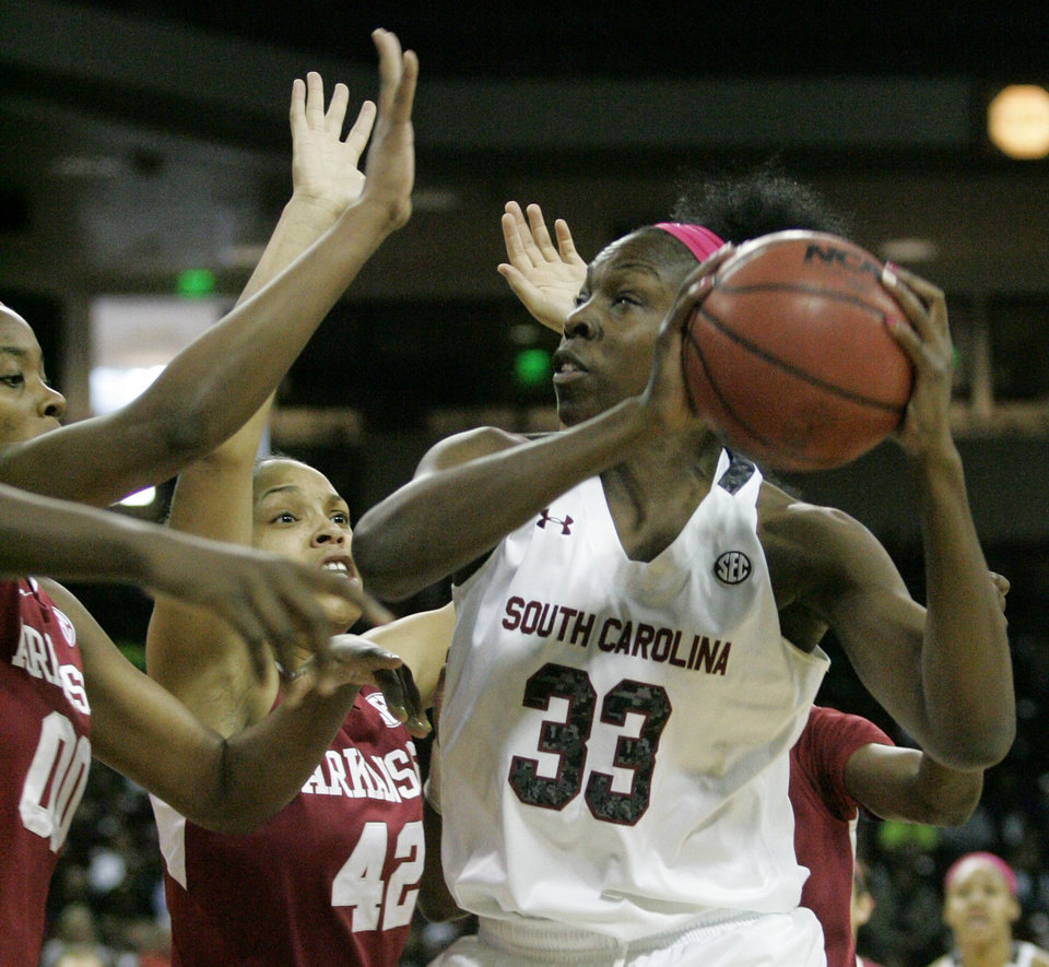 Photo - South Carolina's Elem Ibiam (33) drives for the basket as Arkansas's Jessica Jackson (00) and Jhasmin Bowen (42) try to defend during an NCAA college basketball game on Sunday, Feb. 9, 2014, in Columbia, S.C. (AP Photo/Mary Ann Chastain)
