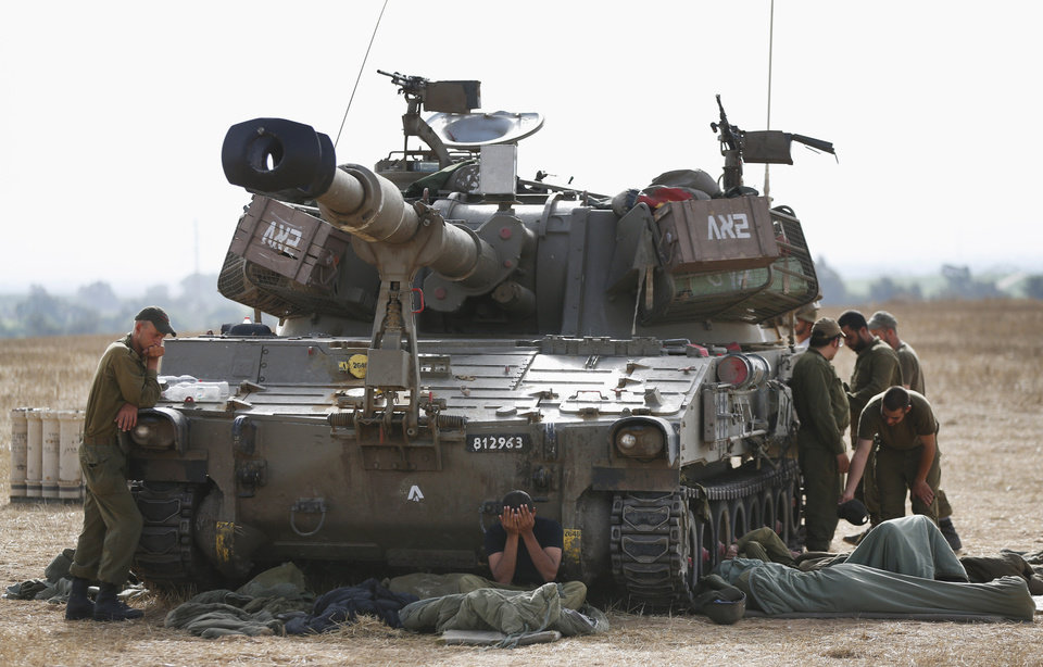 Photo - Israeli soldiers gathering next to their mobile artillery unit begin their day at a position on Israel Gaza border, Saturday, July 12, 2014. Israeli airstrikes overnight targeting Hamas in Gaza hit a mosque its military says concealed the militant group's weapons, in an offensive that showed no signs of slowing down. Israel launched its campaign five days ago to stop relentless rocket fire on its citizens. While there have been no fatalities in Israel, Palestinian officials said overnight attacks raised the death toll there to over 120, with more than 920 wounded. (AP Photo/Lefteris Pitarakis)