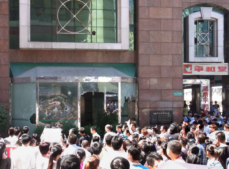 In this Sept. 15, 2012 photo, people crowd outside Japanese supermarket Heiwado after its windows were broken by anti-Japan demonstrators in Shangshain Hunan Province, China. The craggy island specks in the East China Sea aren't even an economic backwater. They have no factories, no highways, no shops, no people � only goats. But the high-pitched row between Beijing and Tokyo over their ownership is exacting a growing toll on Japan, threatening to send its recovery from last year's disasters into reverse. (AP Photo/Kyodo News) JAPAN OUT, MANDATORY CREDIT, NO LICENSING IN CHINA, FRANCE, HONG KONG, JAPAN AND SOUTH KOREA