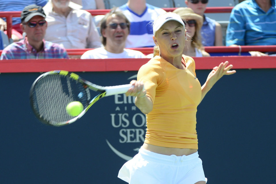 Photo - Caroline Wozniacki, of Denmark, returns to Serena Williams at the Rogers Cup tennis tournament Friday, Aug. 8, 2014,  in Montreal. (AP Photo/The Canadian Press, Paul Chiasson)