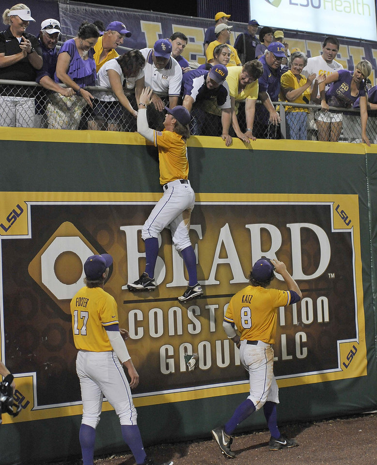 As the LSU team thanks the fans in the outfield, outfielder Raph Rhymes (4), hangs on the wall while thanking the fans for their support as teammates Jared Foster (17) and Mason Katz (8) watch after an NCAA college baseball tournament regional game against Louisiana-Lafayette, Sunday, June 2, 2013, in Baton Rouge, La. LSU won 5-1. (AP Photo/Bill Feig) ORG XMIT: LABF122