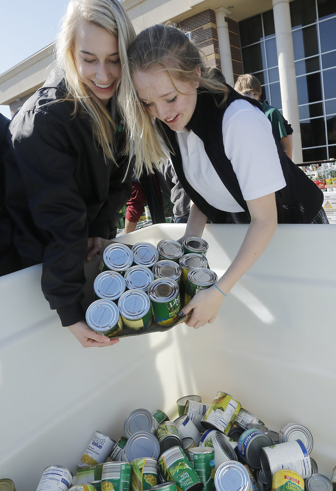 Kate Goetzinger, left, and Paris Rose help to load food collected for the Regional Food Bank of Oklahoma at Bishop McGuinness High School Friday, November 9, 2012.  The school collected 75,660 pounds of food. Photo by Doug Hoke, The Oklahoman