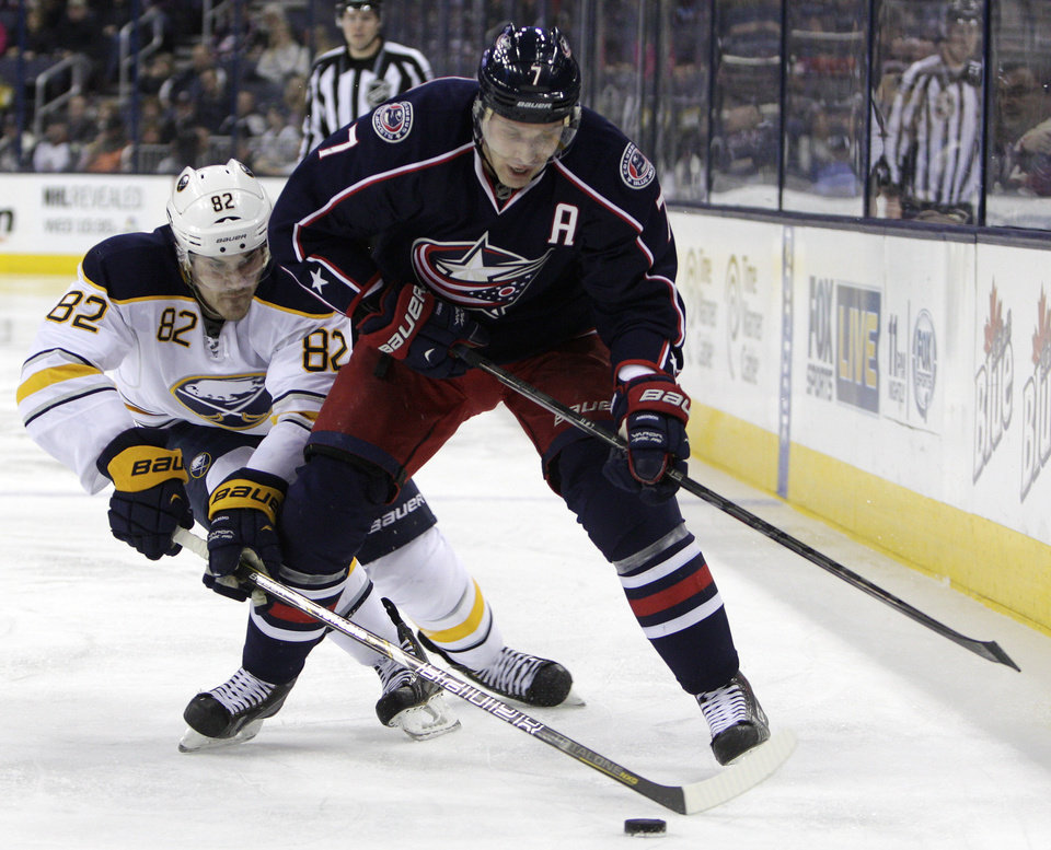Photo - Columbus Blue Jackets' Jack Johnson, right, tries to control the puck as Buffalo Sabres' Marcus Foligno defends during the second period of an NHL hockey game, Saturday, Jan. 25, 2014, in Columbus, Ohio. (AP Photo/Jay LaPrete)