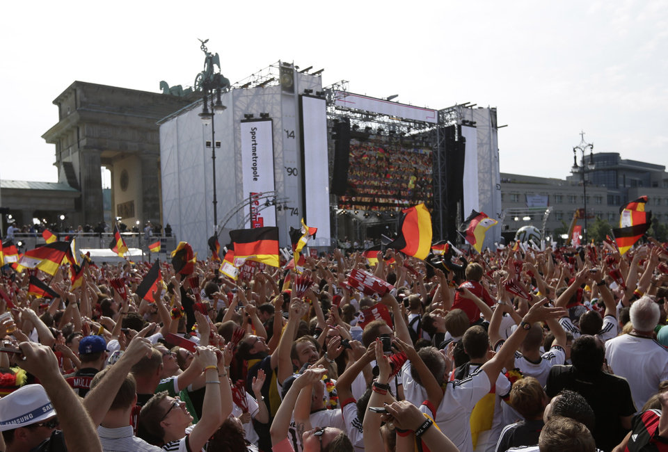 Photo - Fans take pictures of the plane with the German team on board that flies over the stage at the Brandenburg gate prior to the arrival of the German national soccer team in Berlin Tuesday, July 15, 2014. Germany beat Argentina 1-0 on Sunday to win its fourth World Cup title.  (AP Photo/Petr David Josek)