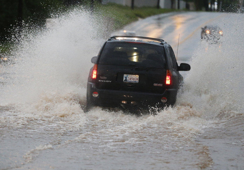 Photo - A vehicle makes its way through deep water following heavy rain in Moore, Okla., Wednesday, May 6, 2015. Forecasters declared a tornado emergency for Moore. (AP Photo/Sue Ogrocki)