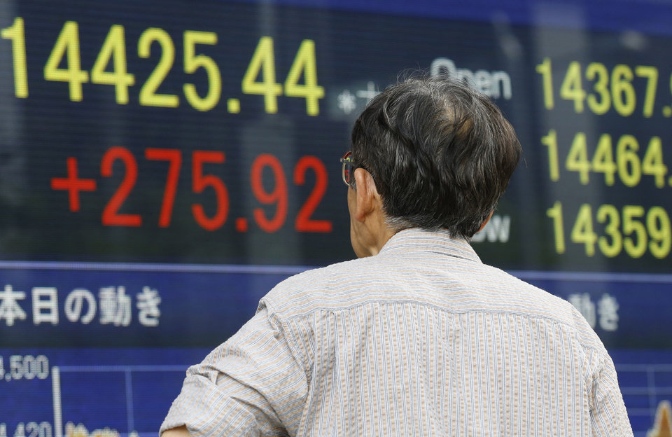 Photo - A man watches an electronic stock indicator of a securities firm in Tokyo, Tuesday, May 13, 2014. Asian stock markets rose after Wall Street indexes hit record highs, with Japan's Nikkei 225 leading gains as the yen weakened. The Nikkei ended up 275.92 points at 14,425.44 on Tuesday. (AP Photo/Shizuo Kambayashi)