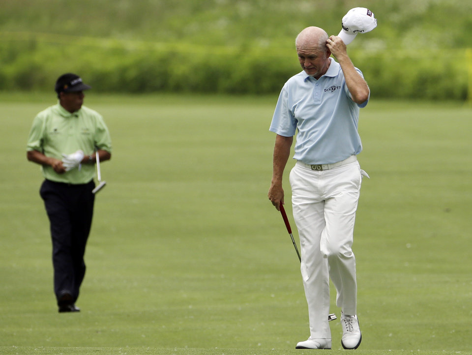 Photo - Roger Chapman reacts as he walks on the first hole after hitting his second shot during the second round of the Encompass Championship golf tournament in Glenview, Ill., Saturday, June 21, 2014. (AP Photo/Nam Y. Huh)
