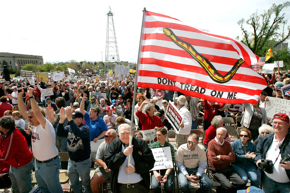 Photo - Bob Meadows of Oklahoma City, holds a flag as he joins Tax Day protesters on the south steps of the State Capitol to protest government spending in Oklahoma City, Oklahoma April 15, 2009.  Photo by Steve Gooch, The Oklahoman