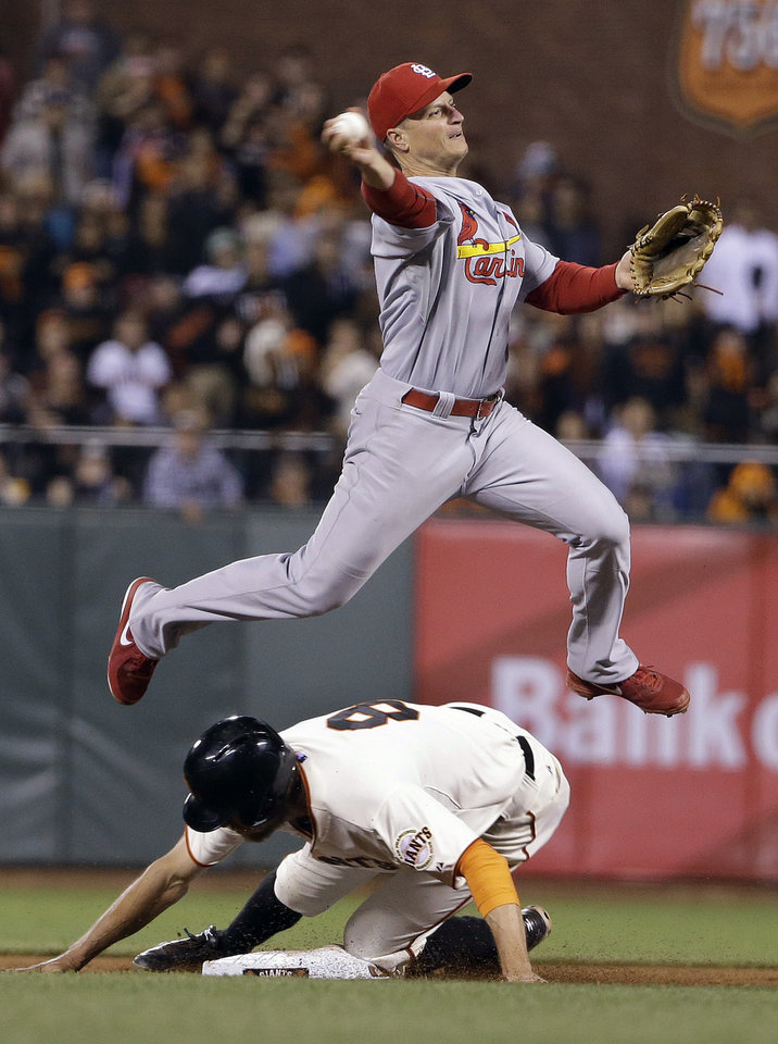 Photo - St. Louis Cardinals second baseman Mark Ellis attempts a double play after San Francisco Giants' Hunter Pence is forced out at second base in the ninth inning of a baseball game Wednesday, July 2, 2014, in San Francisco. The Giants' Buster Posey was safe at first base on the play. St. Louis won the game 2-0. (AP Photo/Eric Risberg)