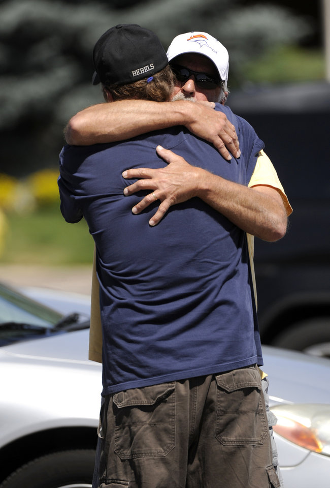 Photo - Two men hug outside Gateway High School in Aurora, Colo., where witnesses are being interviewed by authorities Friday, July 20, 2012. A  gunman wearing a gas mask set off an unknown gas and fired into the crowded movie theater killing 12 people and injuring dozens, authorities said.  The suspect is identified as 24-year-old James Holmes.(AP Photo/The Denver Post, Craig F. Walker) TV, INTERNET AND MAGAZINES CALL FOR RATES AND TERMS ORG XMIT: CODEN238