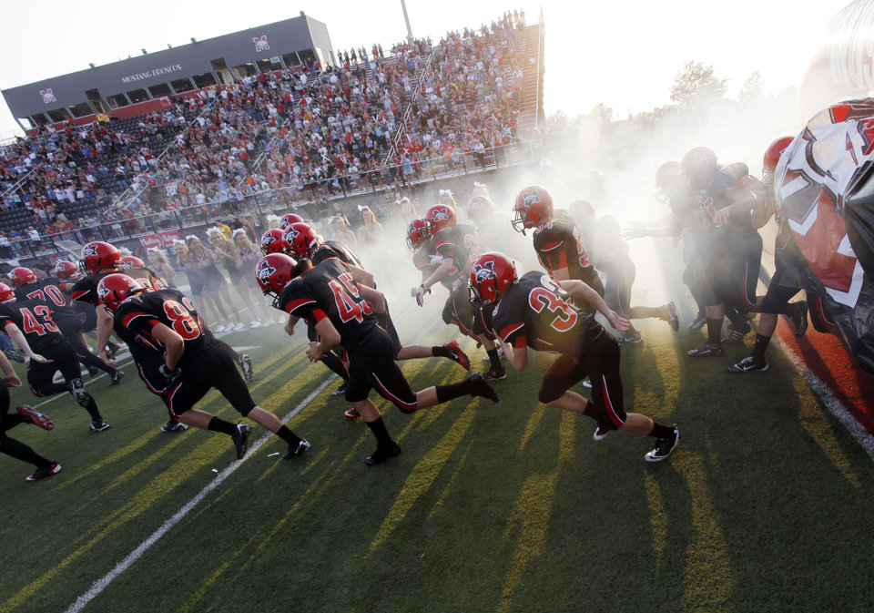 Photo - The Mustang Broncos take the field before a high school football game between Yukon and Mustang at Mustang High School in Mustang, Okla., Friday, Sept. 2, 2011. Photo by Nate Billings, The Oklahoman