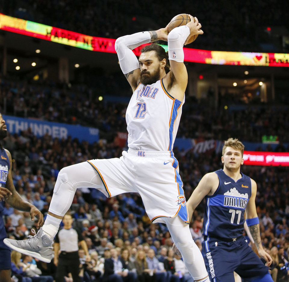 Photo - Oklahoma City's Steven Adams (12) grabs a rebound in front of Dallas' Luka Doncic (77) during an NBA basketball game between the Oklahoma City Thunder and Dallas Mavericks at Chesapeake Energy Arena in Oklahoma City, Monday, Dec. 31, 2018. Photo by Nate Billings, The Oklahoman