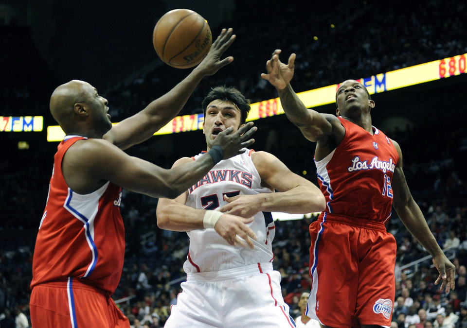 Photo -   Los Angeles Clippers' Lamar Odom (7) and Eric Bledsoe (12) cover Atlanta Hawks' Zaza Pachulia in the first half of an NBA basketball game at Philips Arena in Atlanta, Saturday, Nov. 24, 2012. (AP Photo/David Tulis)