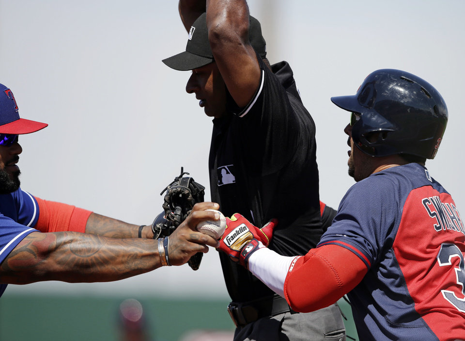 Photo - Cleveland Indians' Nick Swisher is tagged out by Texas Rangers first baseman Prince Fielder, left, as first base umpire Allen Porter tries to get out of the way during the third inning of a spring exhibition baseball game Tuesday, March 25, 2014, in Goodyear, Ariz. (AP Photo/Darron Cummings)