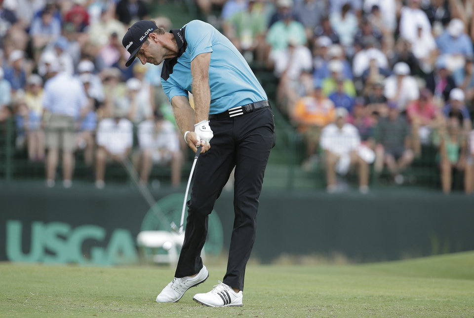 Photo - Dustin Johnson hits his tee shot on the 13th hole during the first round of the U.S. Open golf tournament in Pinehurst, N.C., Thursday, June 12, 2014. (AP Photo/Charlie Riedel)