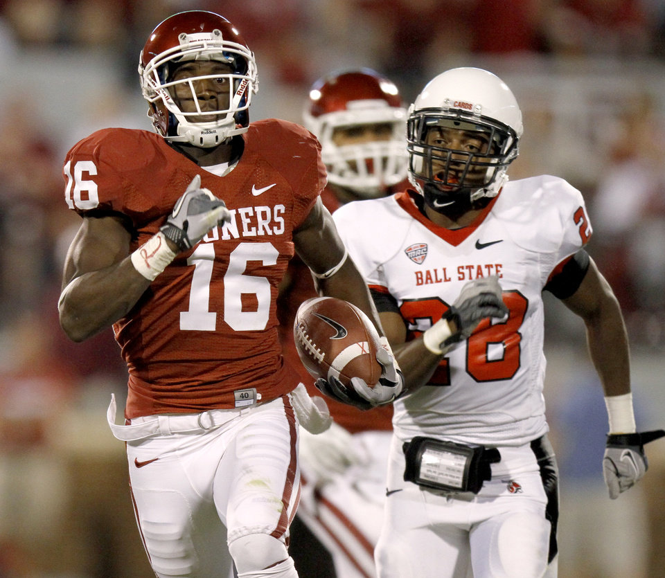 Photo - Oklahoma's Jaz Reynolds (16) runs past Ball State's Andre Dawson (28) after a reception during the college football game between the University of Oklahoma Sooners (OU) and the Ball State Cardinals at Gaylord Family-Memorial Stadium on Saturday, Oct. 01, 2011, in Norman, Okla. Oklahoma's Frank Alexander (84) pressures Ball State's Keith Wenning (10) during the college football game between the University of Oklahoma Sooners (OU) and the Ball State Cardinals at Gaylord Family-Memorial Stadium on Saturday, Oct. 01, 2011, in Norman, Okla. Photo by Bryan Terry, The Oklahoman  Photo by Bryan Terry, The Oklahoman