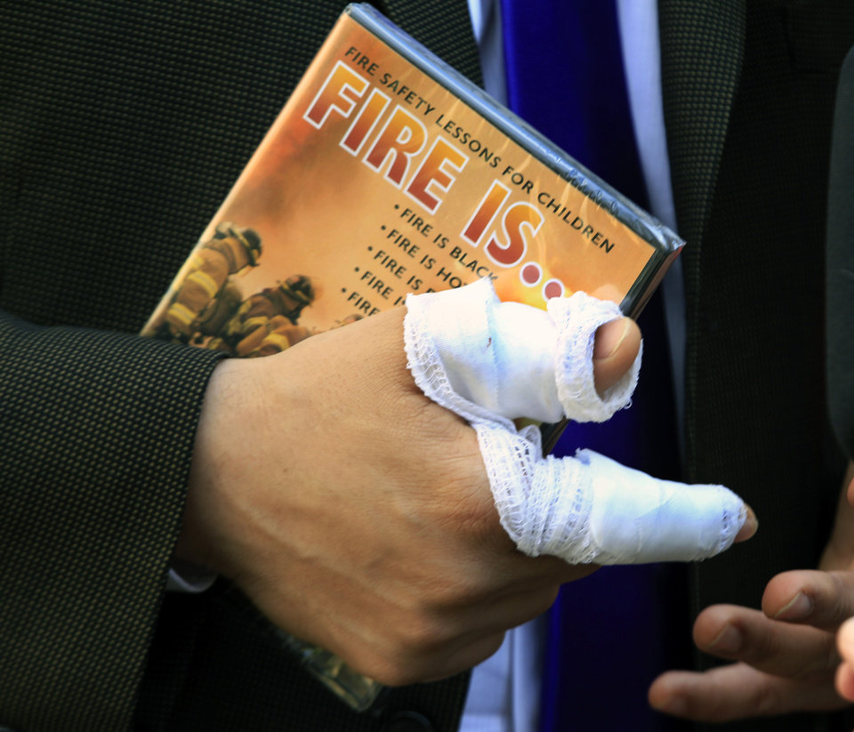 Photo -   Newark Mayor Cory Booker has a bandaged right hand as he holds a children's fire safety video given to him by a well-wisher in Newark, N.J., Friday, April 13, 2012, where he was credited with rescuing a neighbor Thursday from a fire. Booker said Friday he feared for his life as he helped rescue a neighbor from a fire before firefighters arrived. He described how he returned home Thursday night and saw his neighbor's home engulfed in flames. The woman Booker helped save is in stable condition. (AP Photo/Mel Evans)