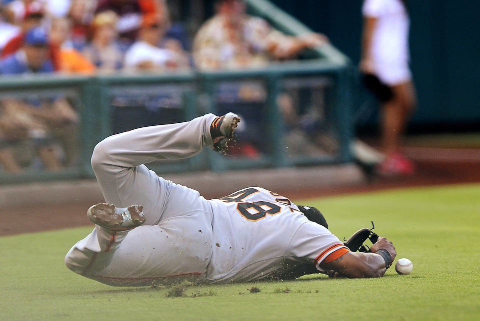 Photo - San Francisco Giants third baseman Pablo Sandoval dives for a pop up foul hit by Philadlephia Phillies' Ben Revere in the first inning of a baseball game on Tuesday, July 22, 2014, in Philadelphia. (AP Photo/Michael Perez)