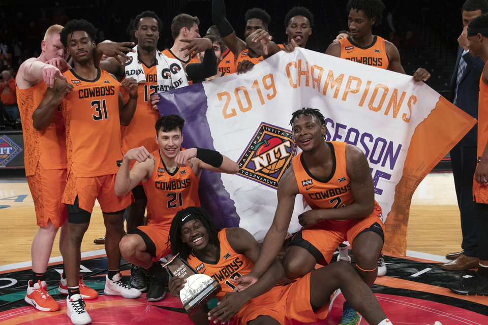 Photo -  Oklahoma State players pose with the NIT Season Tip-Off championship banner. [AP Photo/Mary Altaffer]