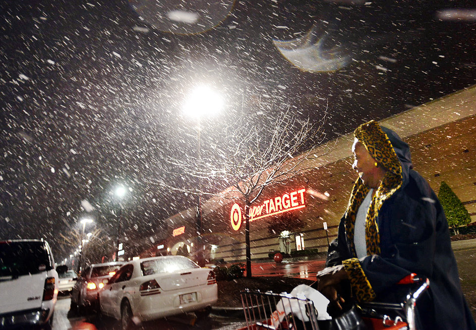 Photo - Ollie Gatheright  leaves the Target store off Durham Chapel Hill Boulevard during a snowy evening, Tuesday,  Jan. 21, 2014, in Durham, N.C. (AP Photo/The Herald-Sun, Bernard Thomas)